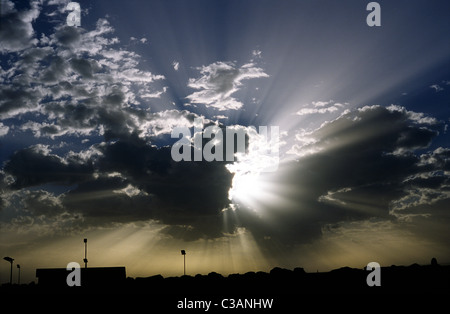 Sun breaking through the clouds early morning over Mgarr ferry terminal on the Maltese island of Gozo. - Stock Photo