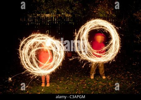 Children with sparklers in a garden - Stock Photo