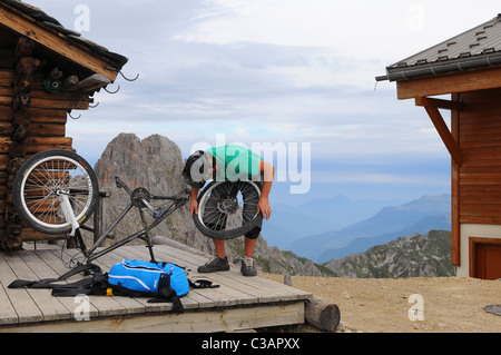 A mountain biker repairs a punctured tire at the top of the Courchevel ski resort in France - Stock Photo