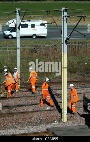 Hi-Visibility Babcock Rail Engineers repairing railway train lines at Beattock Summit; Safety & construction, Network - Stock Photo