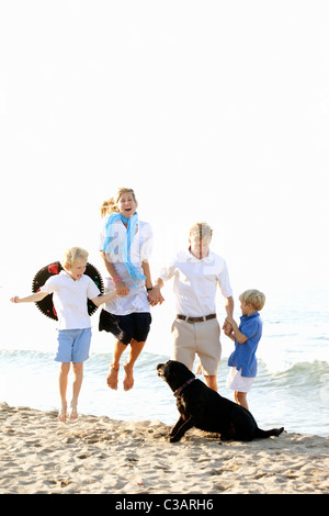 family walking on beach with dogs - Stock Photo
