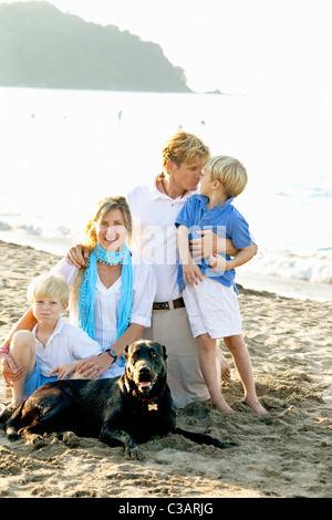 portrait of family on beach with dogs - Stock Photo