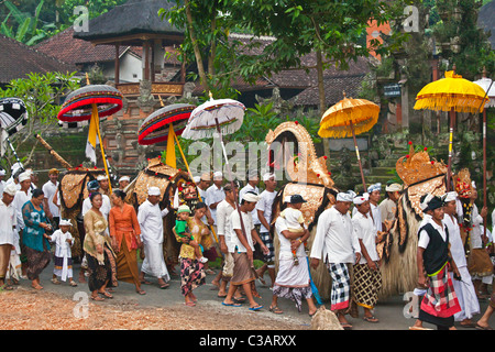 BARONG COSTUMES used in traditional LEGONG dancing are carried during a HINDU PROCESSION for a temple anniversary - Stock Photo