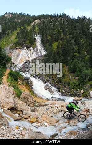 A mountain biker rides past a stream below a waterfall in the Les Avals area of the Courchevel ski resort in France - Stock Photo