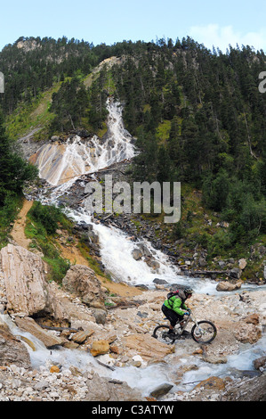 A mountain biker rides past a stream below a waterfall in the vallée des Avals area of the Courchevel ski resort - Stock Photo