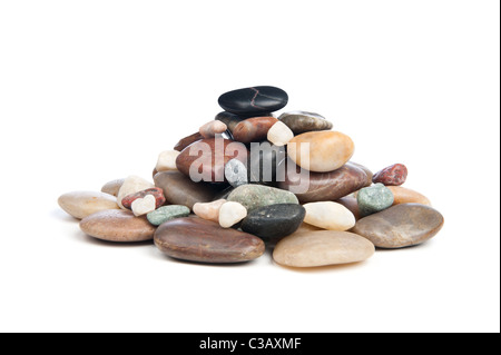 A pile of smooth, shiny river rocks on a white background. - Stock Photo