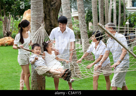 Portrait of a happy family playing on a hammock - Stock Photo