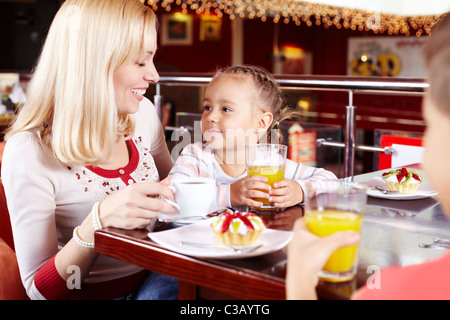 Portrait of cute children and their mother in cafe - Stock Photo