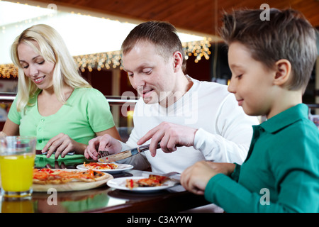 Portrait of family of three having lunch in pizzeria - Stock Photo