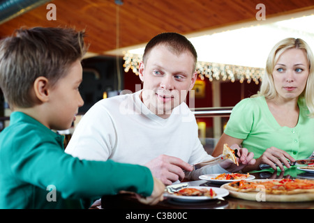 Portrait of family of three eating pizza in cafe - Stock Photo