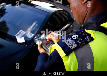 A traffic warden issues a parking ticket - Stock Photo