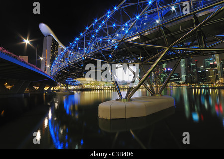 A long exposure shot of the Helix Bridge with the Marina Bay Sands Hotel and Integrated Resort. - Stock Photo