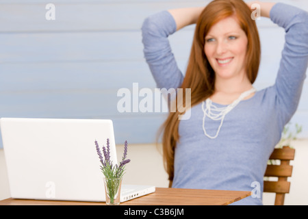 Summer terrace redhead woman with laptop in garden - Stock Photo