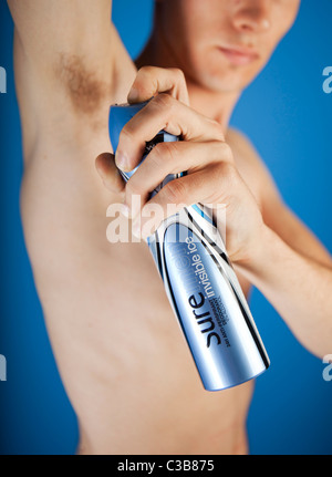 Illustrative image of a man using Sure for Men Invisible deodorant. A Unilever brand. - Stock Photo