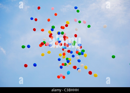 Colourful Helium balloons released into the blue sky at a celebration - Stock Photo