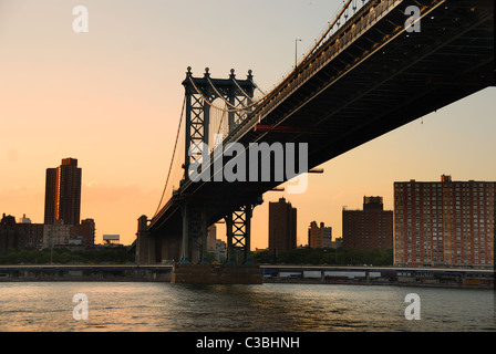 New York City Manhattan Bridge over East River with skyline after sunset night view illuminated with lights from - Stock Photo