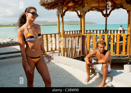 A young women in a bikini with a male friend at Hellshire beach near Kingston, Jamaica. - Stock Photo