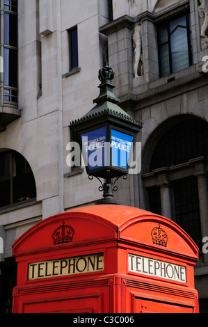 Red Telephone Box and Blue Metropolitan Police Lamp, Agar Sreet, London, England, UK - Stock Photo