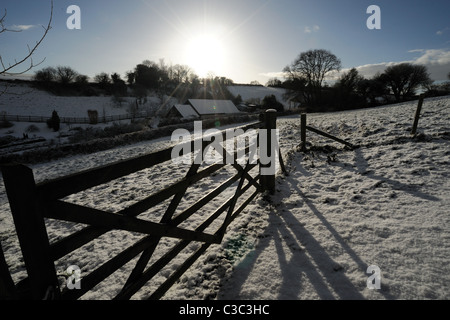 Snowy landscape, 5 bar gate, shadows and low sun on a cold winter morning in East Devon - Stock Photo