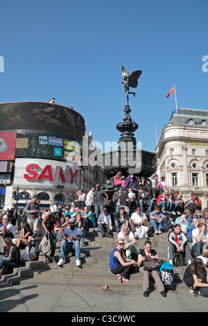 Crowds of tourist enjoying the sun under the statue of Anteros (it is NOT Eros) in Piccadilly Circus, London, UK. - Stock Photo