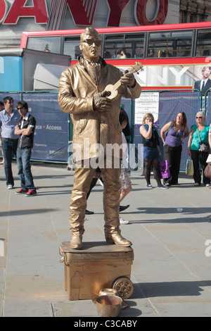 A street artist dressed as a gold plated Elvis Presley entertaining visitors to London's Piccadilly Circus, UK. - Stock Photo