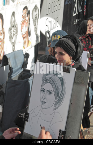 A visitor to London having her portrait drawn by a street artist on Leicester Square, London, UK. - Stock Photo