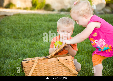 Cute Twin Brother and Sister Toddlers Playing with Apple and Picnic Basket in the Park. - Stock Photo