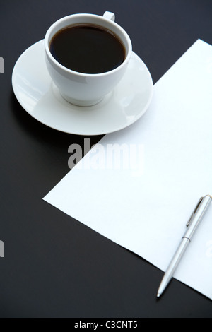 Close-up of cup of coffee, paper and pen on the table - Stock Photo