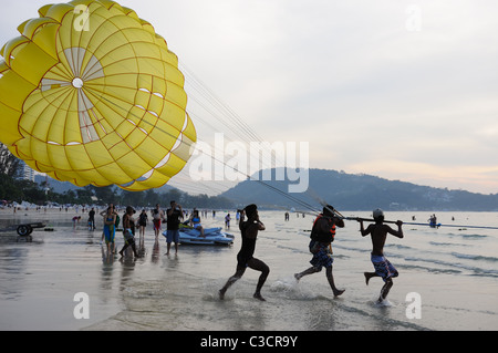 Unidentified man (in the middle) parasails at sunset on FEB 6,2011 at Patong Beach, Phuket, Thailand - Stock Photo