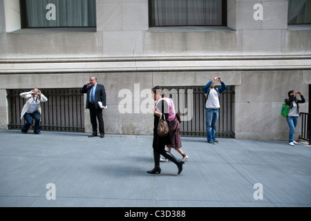 Tourists take pictures of the New York Stock Exchange building, Financial District, New York, USA. - Stock Photo