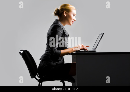 Photo of pretty secretary typing on laptop at workplace - Stock Photo