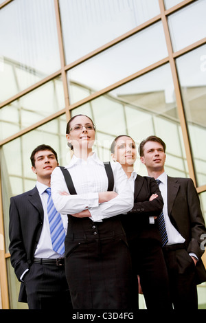Several business leaders standing in row and looking forwards with successful woman in front