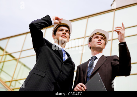 Photo of two co-workers discussing work while one of them showing something to colleague - Stock Photo