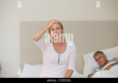 Woman having a headache while her husband is sleeping - Stock Photo