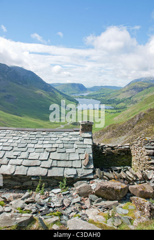 Looking over the slate roof and stone walls of the bothy towards Buttermere in the Lake District Cumbria north west - Stock Photo