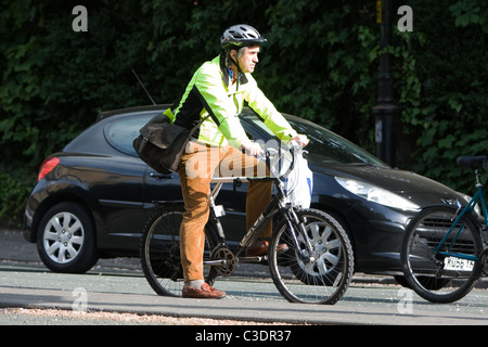 Man on bike wearing a Hi Vis vest - Stock Photo