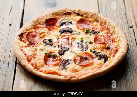 pepperoni and mushrooom pizza on rustic table - Stock Photo
