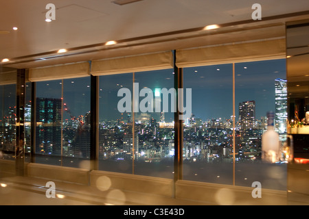 View on Tokyo and skytower by night through windows with some reflection of the interior - Stock Photo
