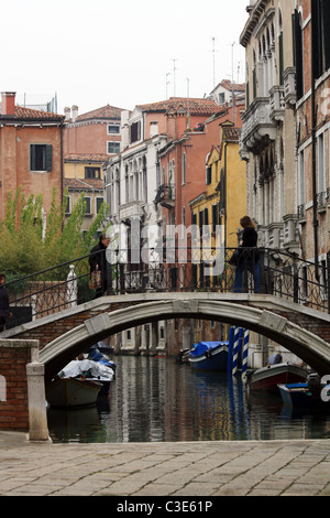 Picturesque view of a women crossing a small bridge over a canal in Venice, Italy - Stock Photo