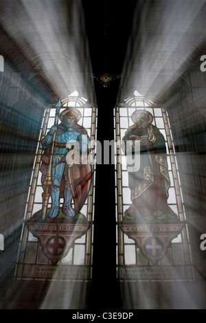 stain glass windows in church with light shining through - Stock Photo