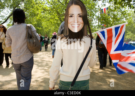 A young girl waves the union flag wearing a mask of Kate Middleton. - Stock Photo