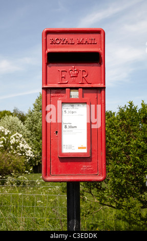 Royal mail post box on road side in rural setting. Showing small red post box with trees, shrubs blue sky clouds. - Stock Photo