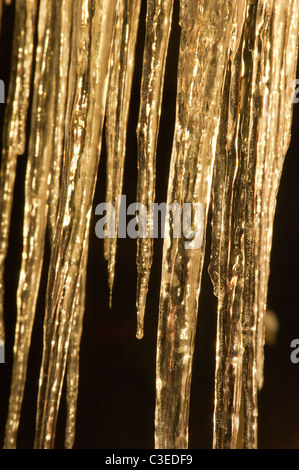 Icicles hanging from the eaves of a house are illuminated against the night sky in Seeley Lake, Montana. - Stock Photo