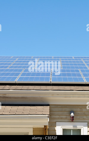 Solar panels on roof of building on a sunny blue sky day. USA - Stock Photo