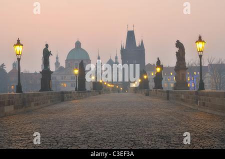 Charles Bridge in Prague during the sunrise, Bohemia, Czech Republic. - Stock Photo