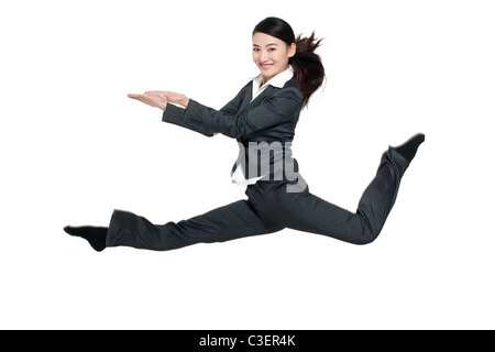 A businesswoman leaping mid-air - Stock Photo