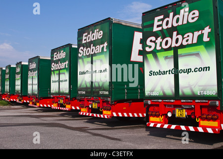 Row of Parked Eddie Stobart trucks trailers & containers at Lorry Halt  Row of Livery AEC Scania 440 haulage vehicles. - Stock Photo