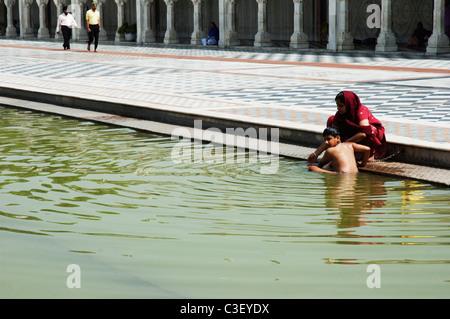 Woman getting her son bath in a pond at a gurudwara, Gurudwara Bangla Sahib, New Delhi, India - Stock Photo