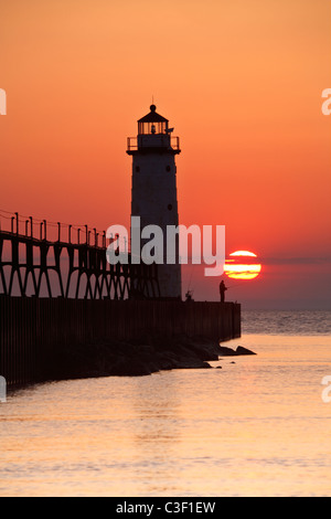 A lone fisherman is silhouetted at the base of the lighthouse on a summer evening at 5th Avenue Beach in Manistee, - Stock Photo