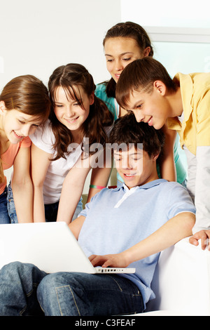 A boy showing something on a laptop to his friends - Stock Photo